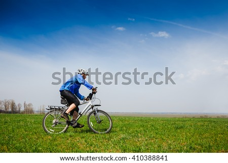 Young cyclist cycling in the spring park