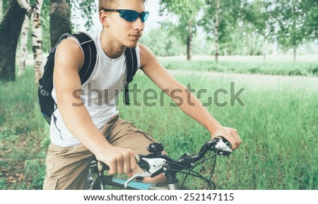 Young cyclist man with backpack riding on bicycle in summer park