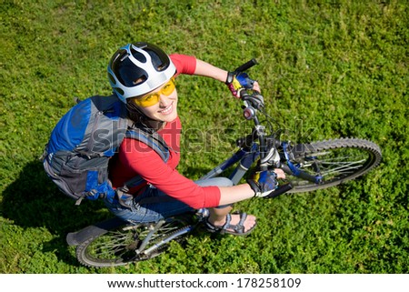 Young cyclist on a mountain bike on green grass - stock photo