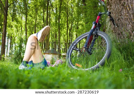 Young cyclist relaxation lying in the fresh green grass   - stock photo