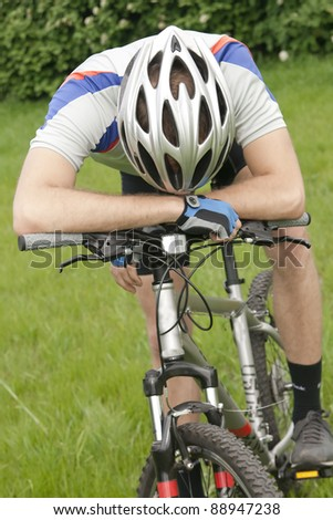 young cyclist stopped, tired - stock photo