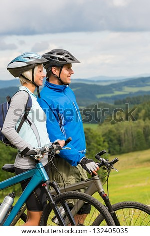 Young cyclists in helmet with bicycles watching scenic landscape - stock photo