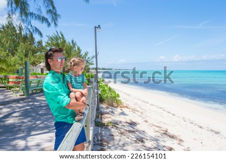 Young dad and his daughter walking on tropical island - stock photo