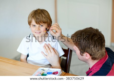 Young dad painting flag on face of little son for football or soccer game. Kid boy fan happy about game of team in champions league. Selective focus. Happy family of two - stock photo