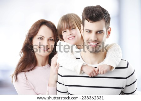 Young dad piggybacking her daughter while standing with her wife together.  - stock photo