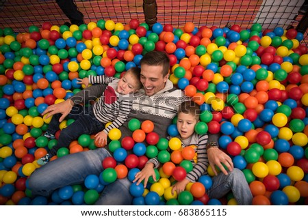 Young dad plays with kids at pool with colorful balls in a children's playroom