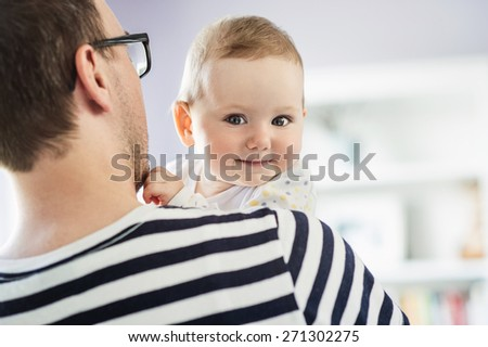 Young daddy holding his daughter in his arms - stock photo