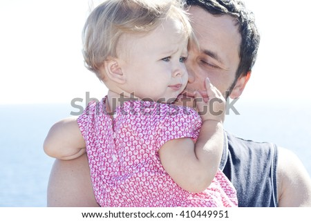 Young daddy holding his daughter in his arms. Pretty looking little charming blond beauty with beautiful blue eyes. Father gently kisses his little girl.  Parenthood concept. Colorful photo. - stock photo