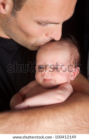 Young daddy kissing his 18 days old little baby son - stock photo
