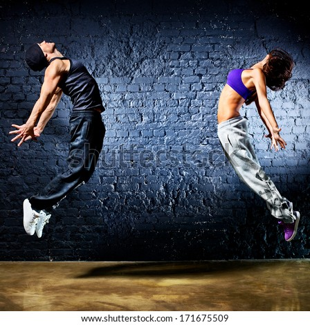 Young dancer couple jumping. On wall background. - stock photo