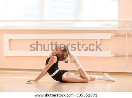 Young dancer doing an exercise at ballet class  - stock photo