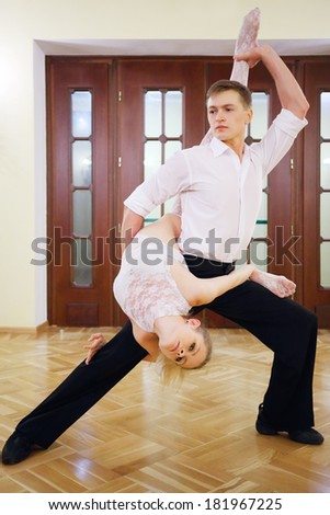 Young dancer holds ballerina upside down in white costume near door in room