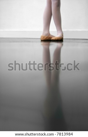 Young dancer in 5th position.. low angle shot of just feet and legs - this view has had the color removed from the floor and wall. - stock photo