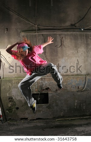 Young dancer jumping on a street next to old grungy wall