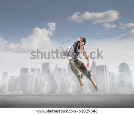 Young dancer jumping with cityscape on the background - stock photo
