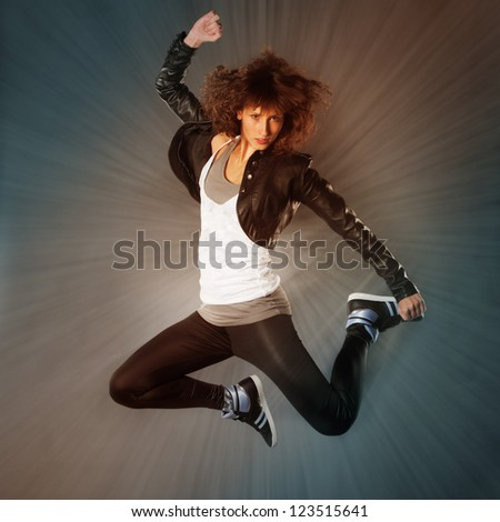 Young dancer jumps in the air with sunbeams in background - stock photo