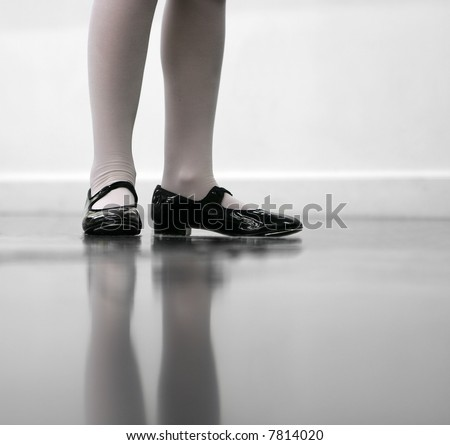 Young dancer... low angle shot of just feet and legs - this view has had the color removed from the floor and wall. - stock photo