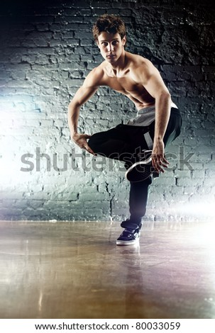Young dancer on wall background. - stock photo