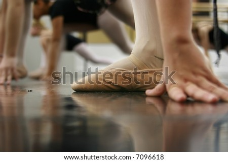 Young dancers are learning - they're waiting to see what the instructor says to do next... low angle shot of just their feet and legs - this view has had the color removed from the floor and wall. - stock photo