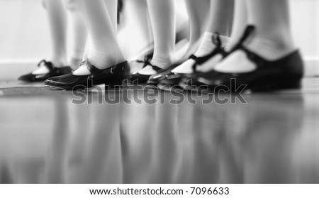 Young dancers are learning - this group is vigorously tapping with tap shoes. Lots of motion - Black and white view - stock photo