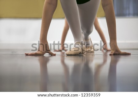 Young dancers are learning to stretch - low angle shot of just their feet and legs - stock photo