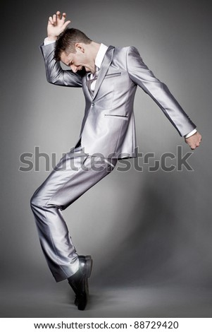 Young dancing  businessman in elegant gray suit. - stock photo