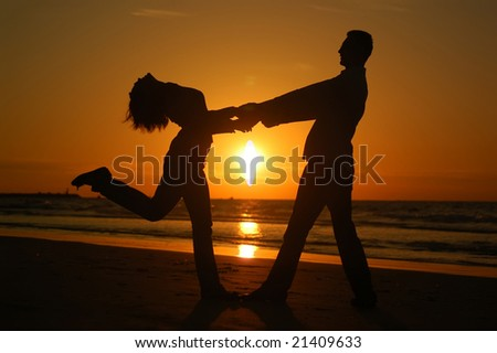 Young dancing couple on a sunset - stock photo