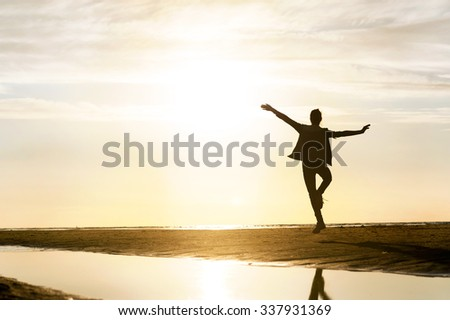 Young dancing girl silhouette in sunbeam at sunset on the beach. Vibrant outdoors horizontal image. Baltic sea coast.