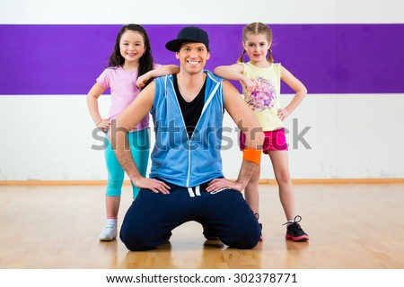 Young dancing teacher training children in modern zumba group choreography  - stock photo