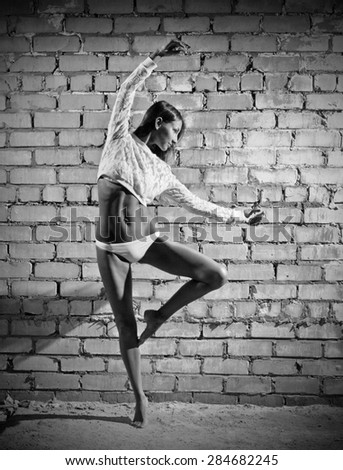 Young dancing woman on grey brick wall background (monochrome version) - stock photo