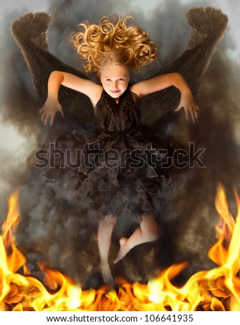 Young dark angel rising from the flames, with an evil look in her face and flames in her eyes. - stock photo