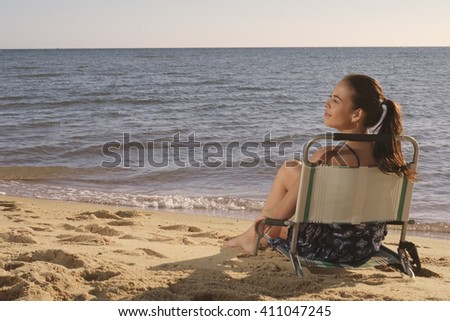 Young dark brown hair woman in dress sitting in chair in warm sunlight from sea turning head on side  - stock photo