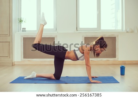 Young dark-haired athletic sporty slim woman doing yoga in the gym in front of the windows, shaker is near by. Toned photo Instagram filter. - stock photo