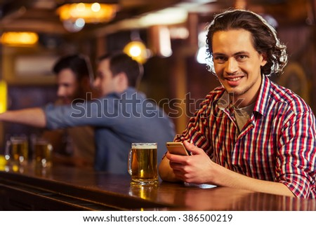 Young dark haired man in casual clothes is smiling, looking at camera, using a smart phone and drinking beer while sitting at bar counter in pub