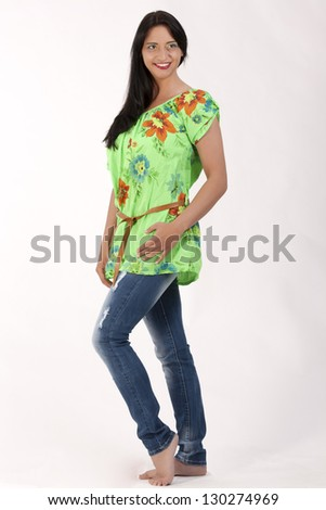 Young dark-haired woman in a floral tunic and trendy jeans / Thank you for the flowers - stock photo