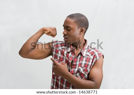 Young dark skinned handsome guy proudly pointing at his biceps showing how strong he is wearing a checkered shirt, isaolated