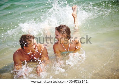 Young dates splashing water while relaxing in the sea - stock photo