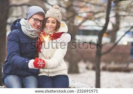 Young dates with Bengal light looking at it while sitting in park outside  - stock photo