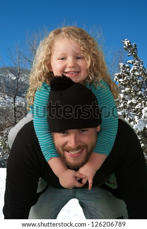 Young daughter riding piggyback on her father's shoulder. - stock photo