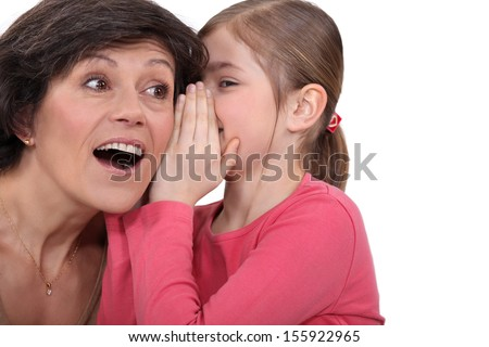 young daughter sharing secret with mom - stock photo
