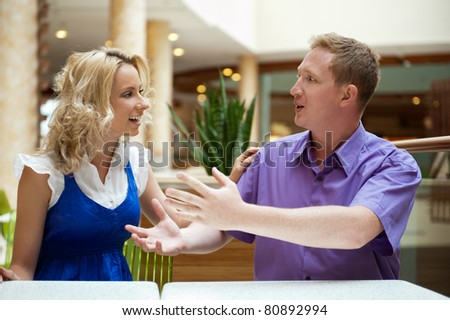 Young debating or talking couple inside mall sitting near the table - stock photo