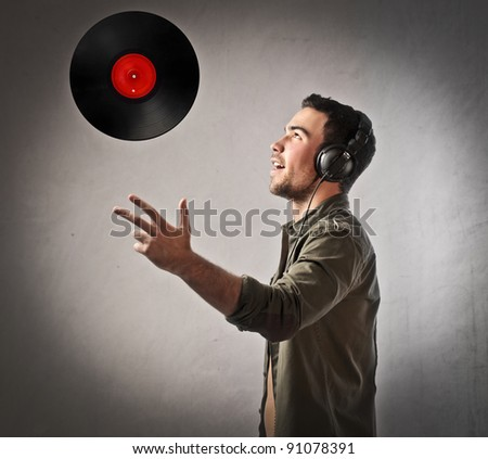Young deejay wearing headphones and throwing a vinyl disc - stock photo