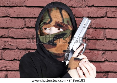 Young delinquent with a gun suggesting a raid or an attack - stock photo