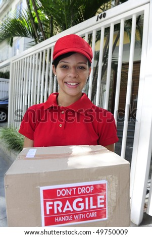 young delivery courier delivering package outdoors - stock photo