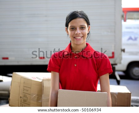 young delivery courier or mover delivering card boards - stock photo