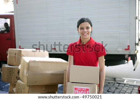 young delivery courier or mover delivering cardboards - stock photo