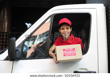 young delivery delivery courier in truck handing over package - stock photo