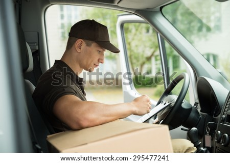Young Delivery Man Checking List On Clipboard In Van - stock photo
