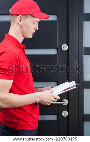 Young delivery man standing at front door - stock photo