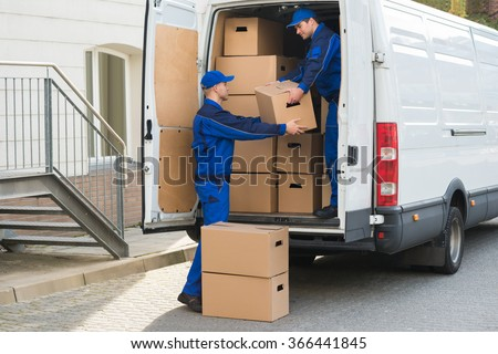 Young delivery men unloading cardboard boxes from truck - stock photo
